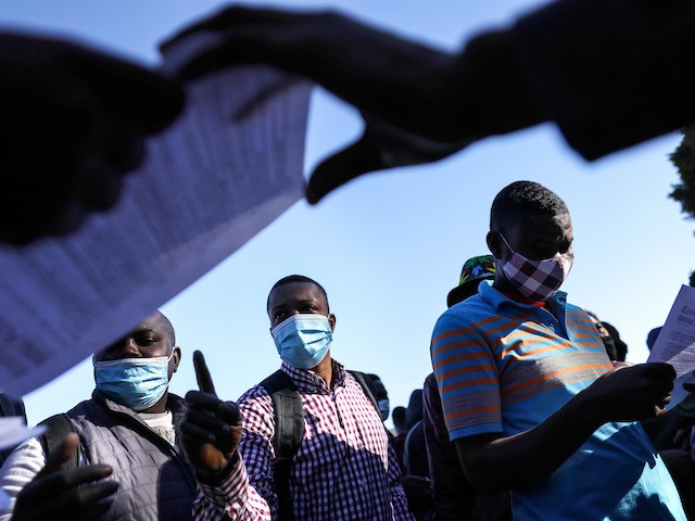 TIJUANA, MEXICO - FEBRUARY 19: People from Haiti who are seeking asylum in the United States wait for flyers explaining updated asylum policies outside the El Chaparral border crossing on February 19, 2021 in Tijuana, Mexico. Those seeking asylum have been waiting months and years in Tijuana and other locations to be allowed into the U.S. to petition for asylum. Starting today, a small group out of an estimated 25,000 asylum seekers with active cases will be allowed into the U.S., a Biden administration move to reverse the Trump administration's 'Remain in Mexico' immigration policy. (Photo by Mario Tama/Getty Images)