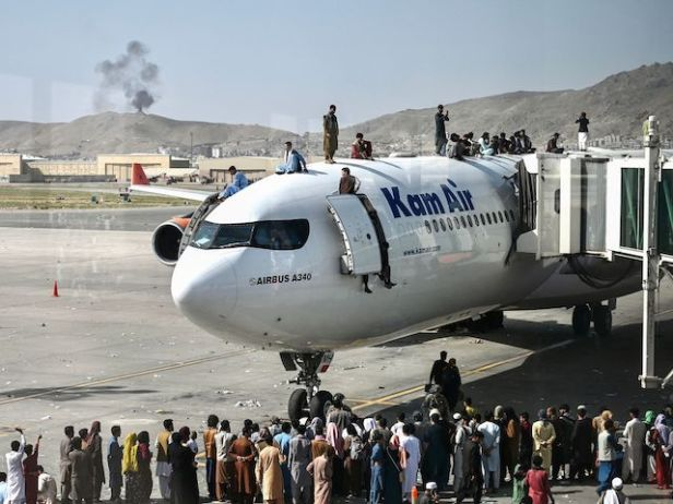 TOPSHOT - Afghan people climb atop a plane as they wait at the Kabul airport in Kabul on August 16, 2021, after a stunningly swift end to Afghanistan's 20-year war, as thousands of people mobbed the city's airport trying to flee the group's feared hardline brand of Islamist rule. (Photo by Wakil Kohsar / AFP) (Photo by WAKIL KOHSAR/AFP via Getty Images)