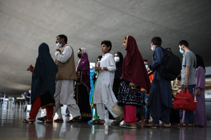 DULLES, VIRGINIA - AUGUST 31: Refugees walk through the departure terminal to a bus at Dulles International Airport after being evacuated from Kabul following the Taliban takeover of Afghanistan on August 31, 2021 in Dulles, Virginia. The Department of Defense announced yesterday that the U.S. military had completed its withdrawal from Afghanistan, ending 20 years of war. (Photo by Anna Moneymaker/Getty Images)