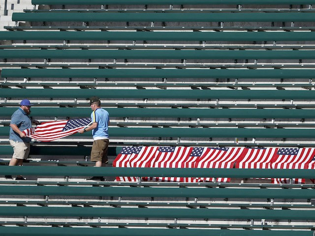 SEATTLE, WASHINGTON - SEPTEMBER 01: Fans fold flags to honor 13 US service members killed in Kabul airport attack after the game between the Seattle Mariners and the Houston Astros at T-Mobile Park on September 01, 2021 in Seattle, Washington. (Photo by Steph Chambers/Getty Images)