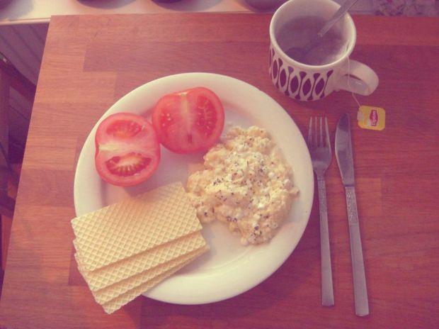 Äggröra med keso, tomat och glutenfria smörgåsrån samt en kopp te.