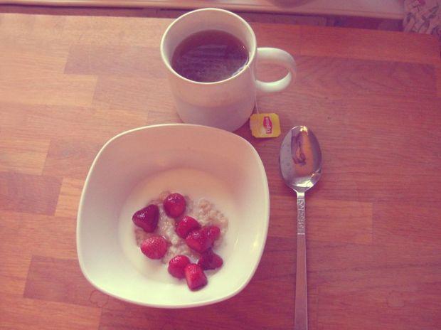 Havregrynsgröt med jordgubbar, mjölk och en kopp te