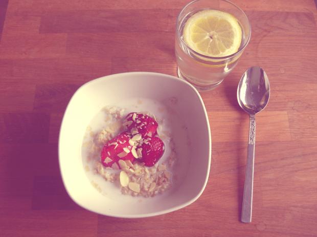 Havregrynsgröt med ägg i, med jordgubbar och mjölk, ett glas citronvatten