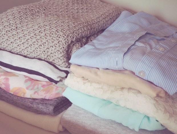 en hög med vikta kläder i garderoben