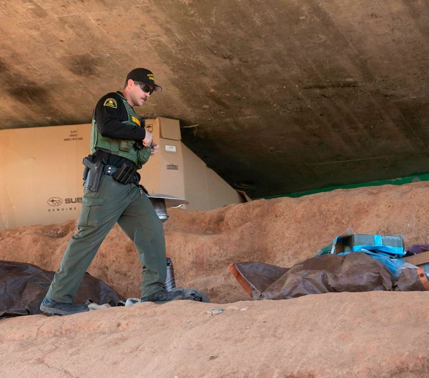Homeless Outreach Team member Deputy Aaron Bert looks for a person who was living under a bridge and had asked for an appointment to talk with them about getting help. (John Gibbins/San Diego Union-Tribune/TNS)