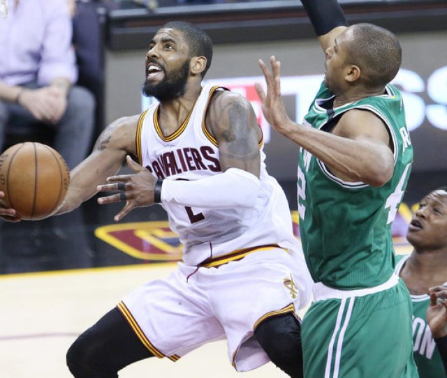 Cleveland Cavaliers Guard Kyrie Irving Drives To The Basket For A Score Guarded By Boston Celtics