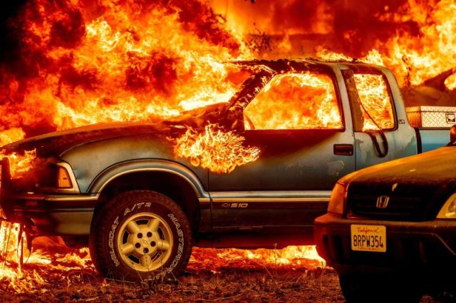 Flames from the Dixie Fire consume a pickup truck on Highway 89, south of Greenville, California, on Thursday, August 5.