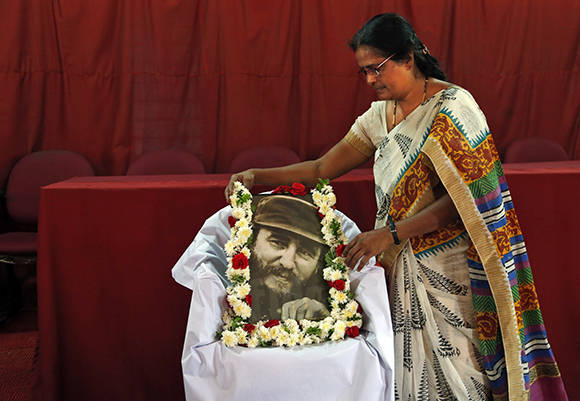 A woman arranges a garland around a photograph of the late Cuban revolutionary leader, Fidel Castro, at a memorial service in Bangalore, India, Monday, Nov. 28, 2016. Castro, who led his bearded rebels to victorious revolution in 1959 and embraced Soviet-style communism to defy the power of 10 U.S. presidents during his half-century of rule in Cuba, died on Friday at age 90. (AP Photo/Aijaz Rahi)