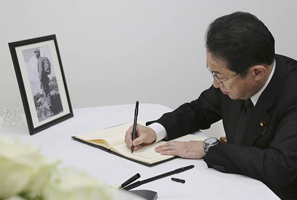 Japanese Foreign Minister Fumio Kishida signs a visitors' book of condolence for the late Cuban revolutionary leader Fidel Castro at Cuban Embassy in Tokyo, Monday, Nov. 28, 2016. Castro, who led his bearded rebels to victorious revolution in 1959, embraced Soviet-style communism and defied the power of 10 U.S. presidents during his half-century of rule in Cuba, died on Friday at age 90. (AP Photo/Koji Sasahara)