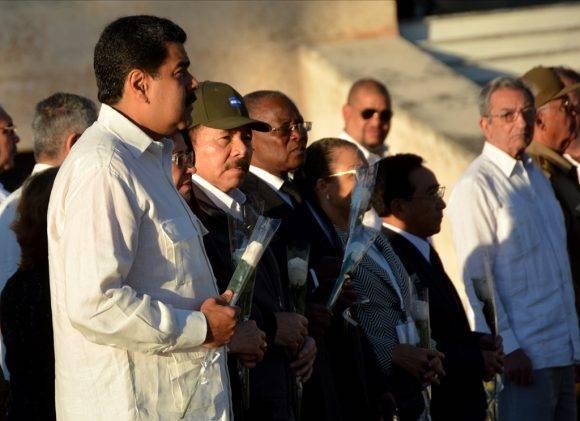 Los presentes, incluidos las escoltas y los compañeros que cuidaron al líder de la Revolución en sus últimos años, depositan rosas blancas en la base del panteón. Foto: Marcelino Vázquez Hernández/ ACN
