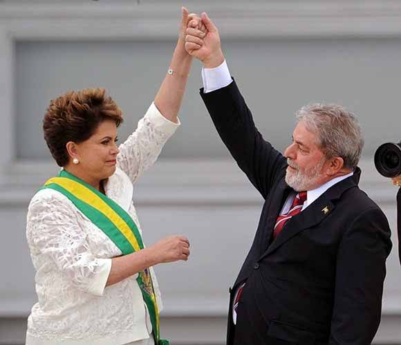 Newly sworn-in Brazilian President Dilma Rousseff (L) and outgoing President Luiz Inacio Lula da Silva raise their hands after she received the presidential sash at the Planalto Palace in Brasilia, January 1, 2011. Rousseff, who beat opposition candidate Jose Serra in a run-off election last October with 56% of the votes, has become the South American nation's first female president. AFP PHOTO/Evaristo SA (Photo credit should read EVARISTO SA/AFP/Getty Images)
