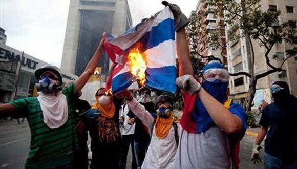 Miembros de la oposición venezolana queman una bandera cubana. Foto: AP.