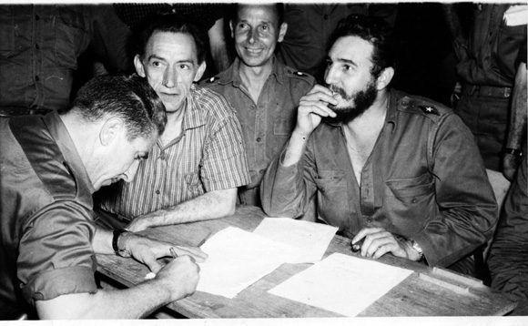 Fidel luego de firmar la Ley de Reforma Agraria le pasa el histórico documento a Luis Orlando Rodríguez, quien lo està  rubricando. Junto al Comandante en Jefe aparecen el médico Comandante Julio Martínez Paez, ministro de Salubridad y el Ministro de Trabajo, Manuel Fernández.