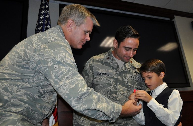 Lt. Gen. Eric E. Fiel, Air Force Special Operations Command commander, hands the Bronze Star medal to Hunter, son of Maj. F. Damon Friedman during a ceremony Nov. 13, 2013, at Hurlburt Field, Fla. Friedman, an AFSOC special tactics officer, was awarded the Bronze Star with Valor for his actions against enemy forces in Afghanistan in April 2010. (U.S. Air Force photo by Master Sgt. Carlotta Holley)