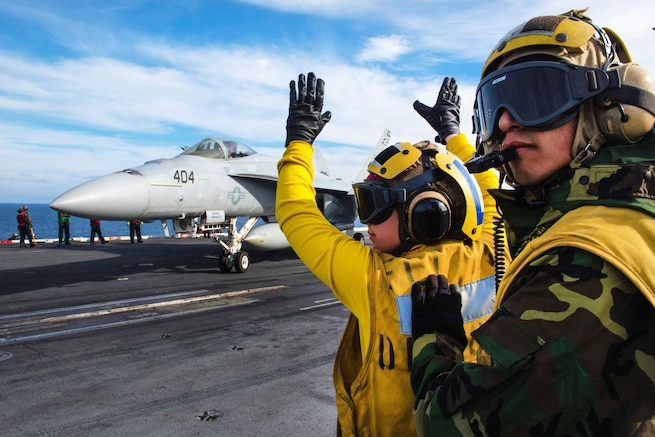 Navy Airman Molly McGuinness directs an F/A-18E Super Hornet onto a catapult on the flight deck while Petty Officer 1st Class Manuel Laguna supervises aboard the USS John C. Stennis in the Pacific Ocean, Jan 22, 2016. Laguna is an aviation boatswain's mate. U.S. Navy photo by Petty Officer 3rd Class Kenneth Rodriguez Santiago