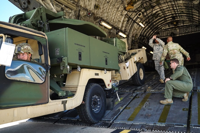 Army Spc. Javier Steele, left, looks into the rear view mirror as he backs a Humvee with an attached trailer into a C-17 Globemaster III aircraft supporting Operation Atlas Strike 17-001 at Fort Bragg, N.C., Feb. 24, 2017. Army photo by Pfc. Liem Huynh