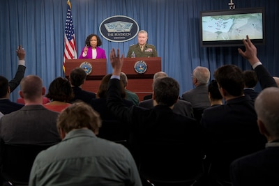A civilian and a Marine stand behind lecterns and take questions from reporters.