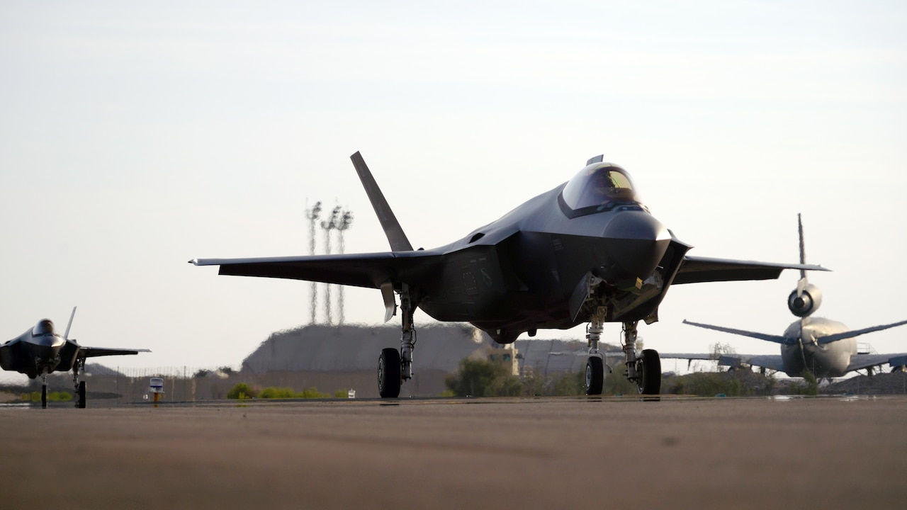 A U.S. military fighter jet sits on a runway near other aircraft.