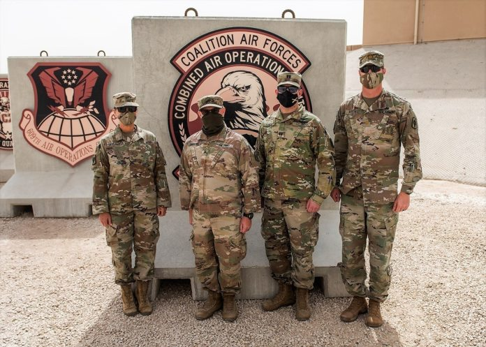 Members of the 130th Field Artillery Brigade  who participated in the Air and Missile Defense Exercise 21 pose for a photo at the Combined Air Operations Center in Souwthwest Asia. From right to left: Chief warrant officer Carol Sprawka, brigade targeting officer; Sgt. Evan Andrews, fire direction non-commissioned officer; Capt. Daniel Vancil, space operations officer; and Maj. Chris Koochel, CAOC liaison officer. AMDEX 21 contributes to the increased lethality and readiness within the Task Force Spartan area of responsibility. Task Force Spartan is committed to establishing strong partnerships and maintaining a ready and responsive force.