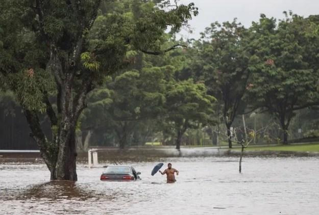 El propietario de un coche, prácticamente sumergido, intenta rescatar objetos personales de su interior, en una avenida afectada por las inundaciones provocadas por el paso del huracán Lane en Hilo, Hawái, Estados Unidos.