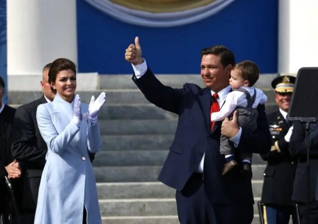 El recién juramentado gobernador de la Florida, Ron DeSantis, saluda a la multitud mientras lleva en brazos a su hijo Mason y junto a su esposa Casey DeSantis, durante la ceremonia de juramento del cargo en el Museo del Capitolio Histórico en Tallahassee.
