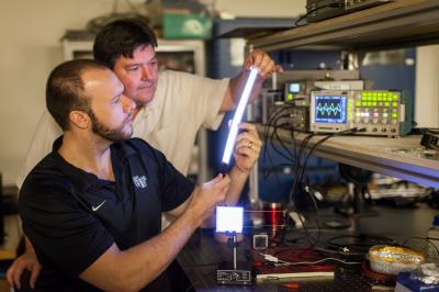 Wake Forest University physics professor David Carroll works with graduate student Greg Smith on new FIPEL lighting technology