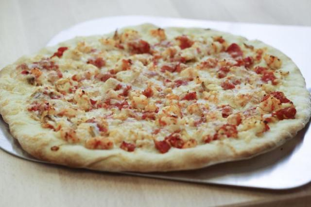 Photo of a pizza with fish and shrimp toppings.