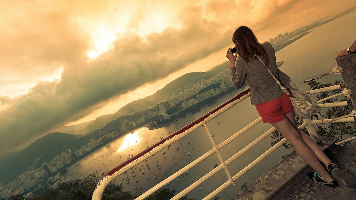 Female tourist taking a picture of the sunset from a look-out point in Rio, Brazil