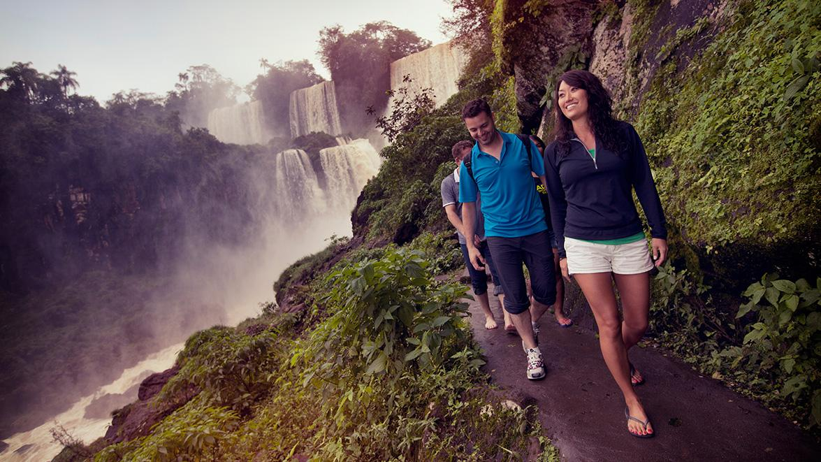 Girl walking with group on a path below the beautiful iguassu falls in argentina