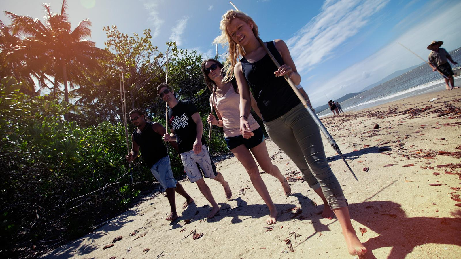 Four tourists walking along a beach in Queensland, Australia with fishing spears