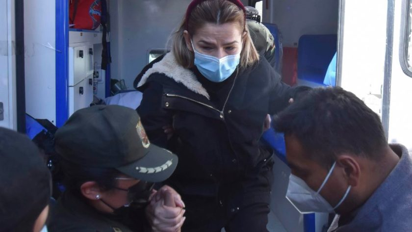 Former Bolivian interim president Jeanine Áñez is assisted by police as she returns to jail after being treated at a hospital