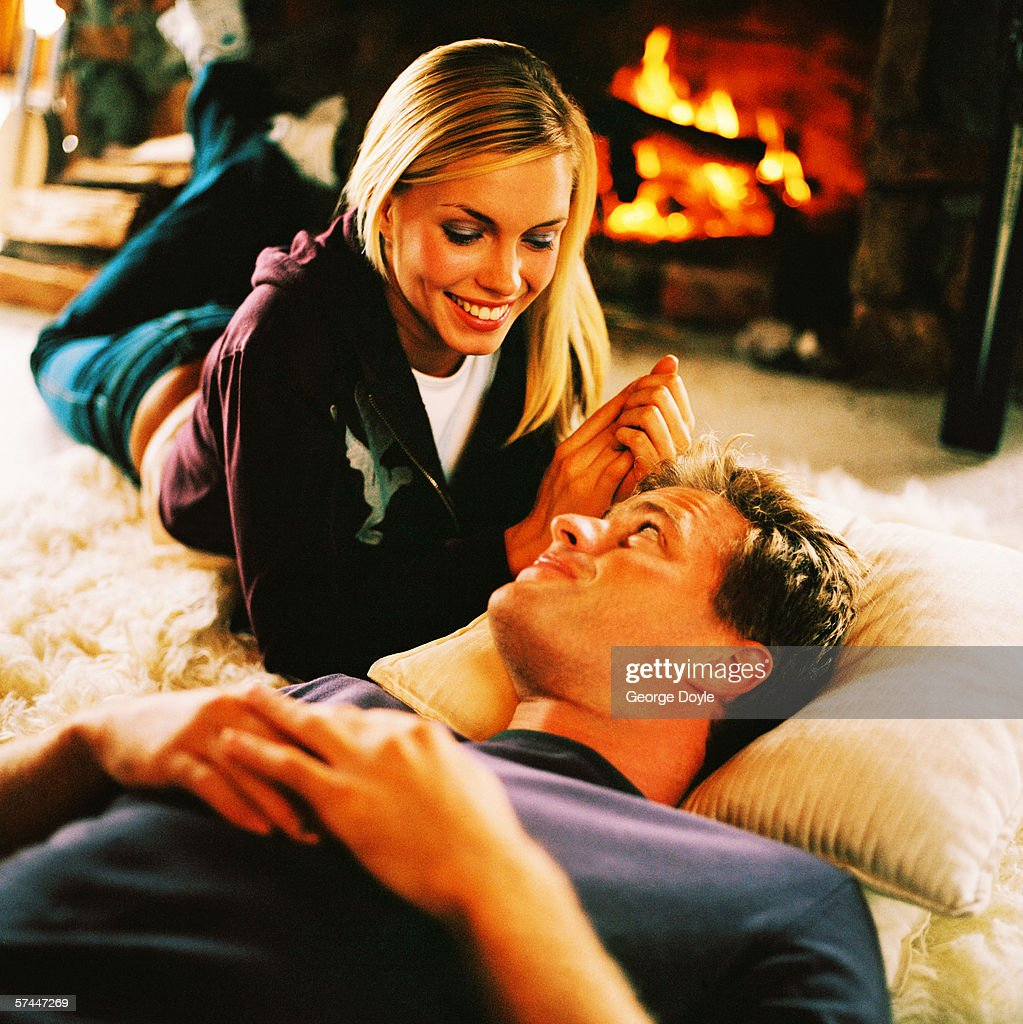 Couple Relaxing In Front Of Fireplace Man Looking At Woman Stock Couple Fireplace Stock Photos And Pictures | Getty Images