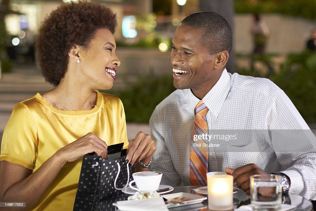 African American Giving Wife Gift Over Dinner Stock Photo