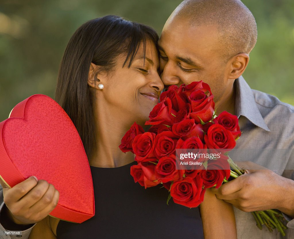 African American Man Giving Valentines Day Gifts To Wife