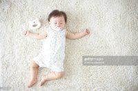 Baby Lying Down On Carpet Sleeping  | Getty Images