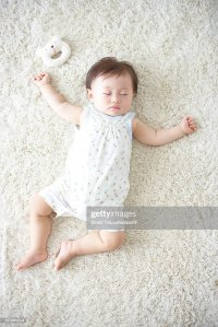 Baby Lying Down On Carpet Sleeping Stock Photo | Getty Images