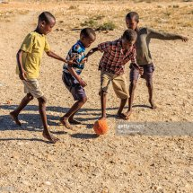 Barefoot African Children Playing Football In Village