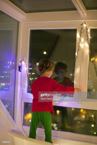 Boy Decorating Christmas Window Stock Photo | Getty Images