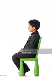 Boy Student Sitting On Small Chair Stock Photo | Getty Images