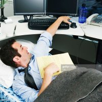 Businessman Lying In Bed In Office Foto de stock