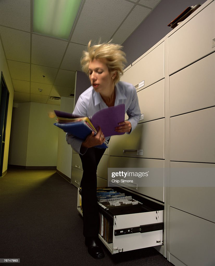 Businesswoman Tripping Over File Drawer Stock Photo