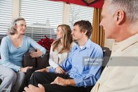 Couple With Parents Talking In The Living Room Stock Photo