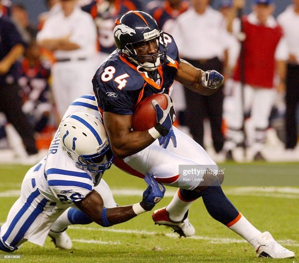 Denver Broncos tight end Shannon Sharpe is tackled by the