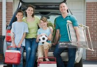 Family Holding Coolers And Beach Chair Behind Car Foto ...