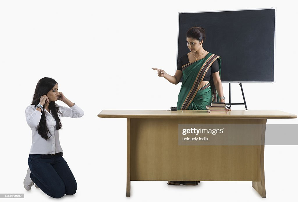 Female Teacher Punishing A Student In A Classroom Stock