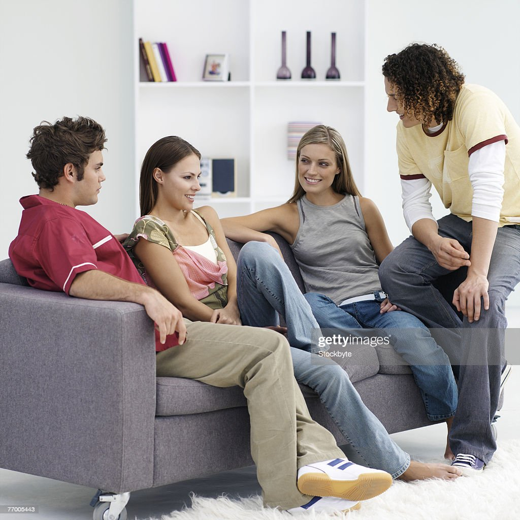 Four Friends Talking In Living Room Stock Photo