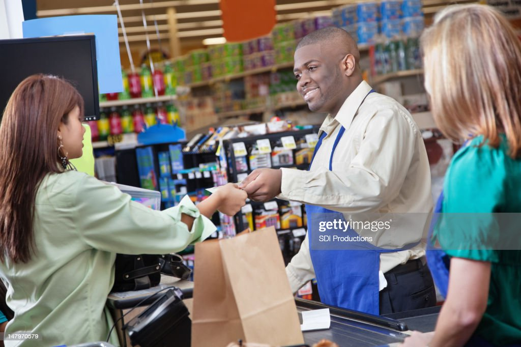 Friendly Grocery Store Clerk Giving Change To Customer Stock Photo  Getty Images
