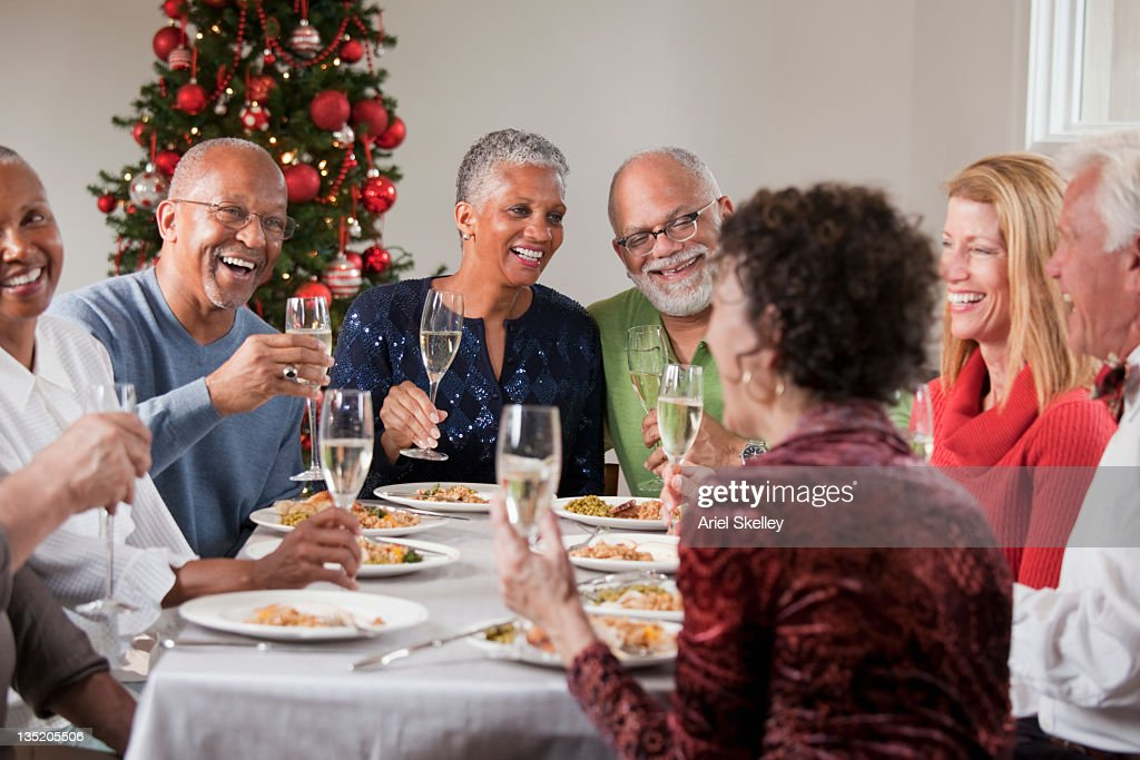 Friends Toasting At Christmas Dinner Party Stock Photo