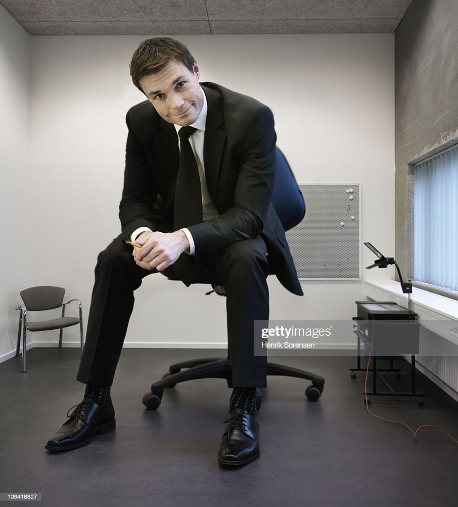 Giant Businessman Sitting On Large Chair In Office Stock