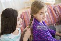 Girl Braiding Friends Hair Stock Photo